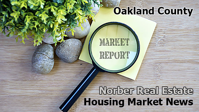 Tabletop has rocks and plant next to a yellow piece of paper with the words market report spelled out beneath a magnifying glass, and more words on the table spell out Oakland County Norber Real Estate Group Housing Market News.