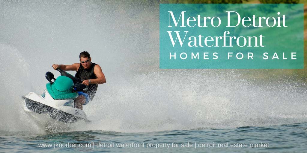 Man riding jet ski on lake. Large text overlay words state Metro Detroit Waterfront Homes For Sale, and smaller texts shows jknorber.com Detroit waterfront properties for sale, Detroit real estate market.