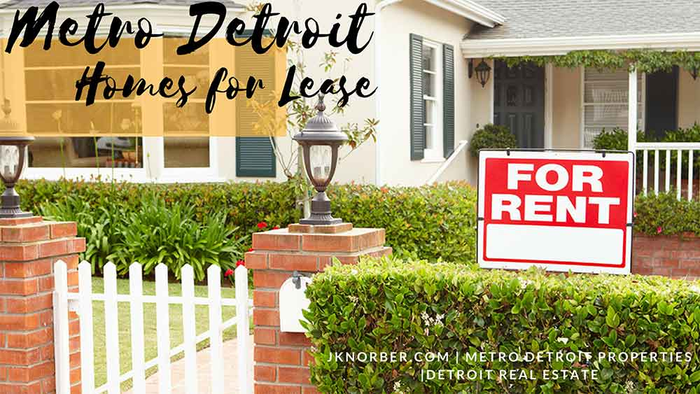 White house with red brick posts on both sides of the entrance. Lights adorn the brick, and there is a white fence door. Shrubbery surrounds the yard with a FOR RENT sign. Text overlay states Metro Detroit Homes for Lease and JKNorber.com, Metro Detroit Properties, Detroit Real Estate.