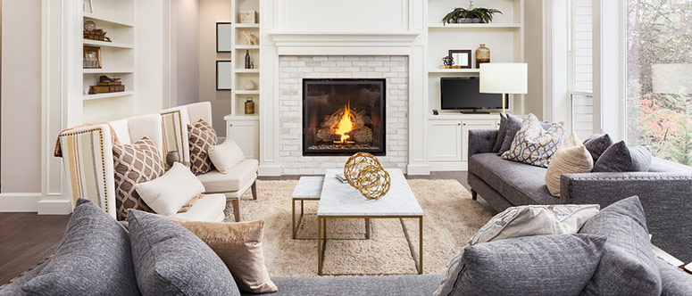 Condo Living Room space with gray couches, lit fireplace adorned with white brick.