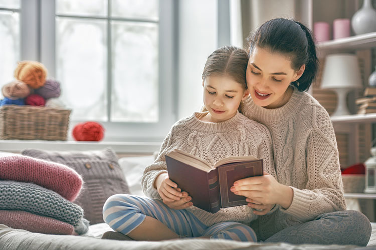 Winter Portrait shows mother in matching sweater reading to her daughter with frosted windows.