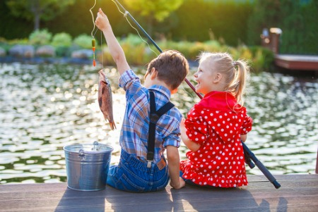 young boy and girl sitting on pier fishing