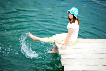 smiling young woman sitting on dock in lake area