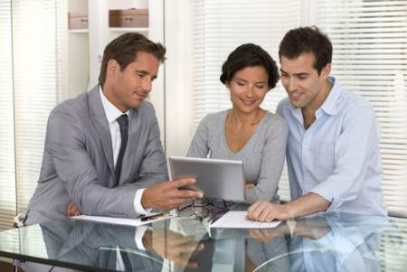 real estate agent with a couple looking at a listing